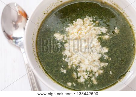 Spinach soup with feta cheese and eggs shot from above. Horizontal shot