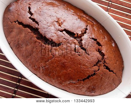 Homemade chocolate cake shot from above in a white bowl. Horizontal shot.