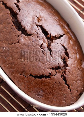 Homemade chocolate cake shot from above in a white bowl. Vertical shot.