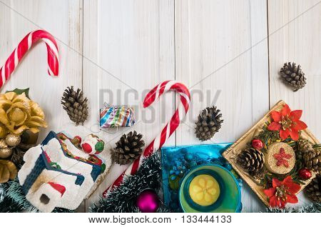Christmas New Year's background with New Year Christmas decoration with pine branches balls candy cane candle with glitter and cones house presents candlestick with flowers on white wooden old boards