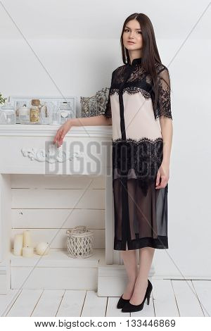beautiful elegant woman with long hair with a gentle make-up in the studio shows elegant white business dress