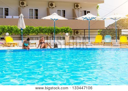 BALI GREECE - APRIL 29 2016: Relax and sunbathe by pool with clear blue water in Resort hotel Atali Village 4 star. Beautiful girl in bikini sitting on edge of pool in middle of day. Bali Rethymno Crete Greece