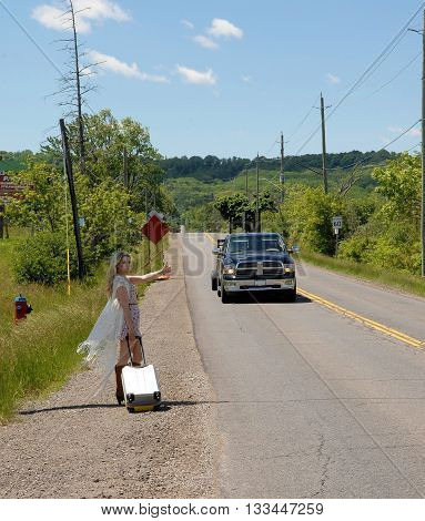 A young blond woman standing on a country read on a summer day looking for a reit carring a suitcase.