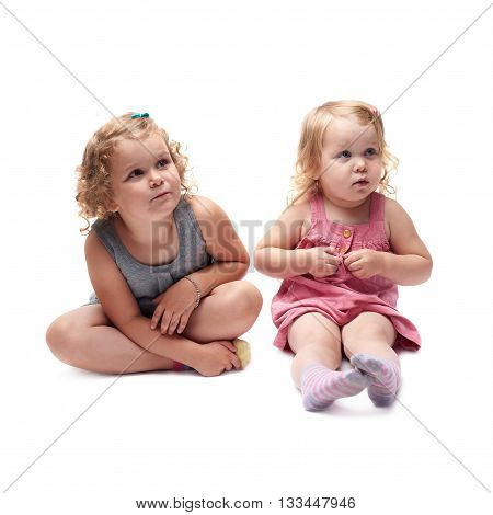 Couple of young little girls sisters with curly hair in gray and pink dress sitting over isolated white background