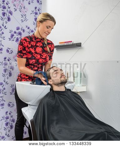 Hairstylist Drying Male Customer's Hair In Salon