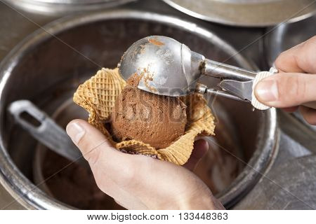 Hands Scooping Ice Cream Into Waffle Bowl At Shop