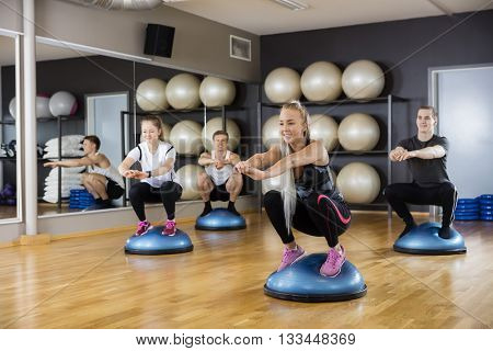 Friends Doing Squatting Exercise On Bosu Ball In Gym