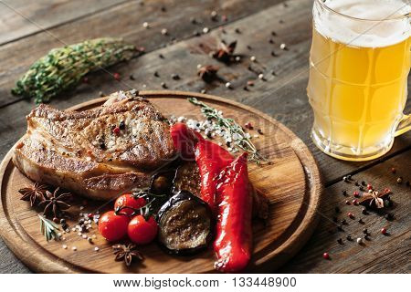 Grilled steak, spices and beer on wooden background. Front view on catering platter with steak and grilled vegetables with glass of beer. Grilled meat, paprika, eggplant and tomato with cold beer