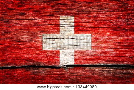 Switzerland flag painted on the old cracked wood with worn-out paint. Grunge look.