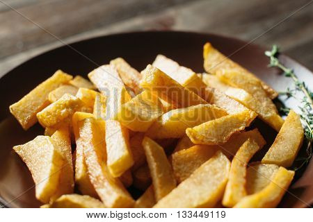 Fried potato in brown clay bowl clos-up. Front view of plate with fried potato and rosemary. Focus on French fries. Concept of health rustic food