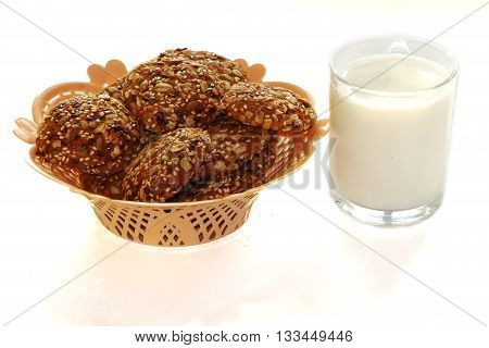 Cookies in a basket and a glass of milk on a white background