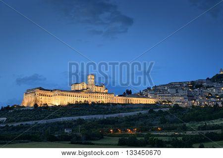 Illuminated cityscape Assisi basilica and monastery in Umbria Italy