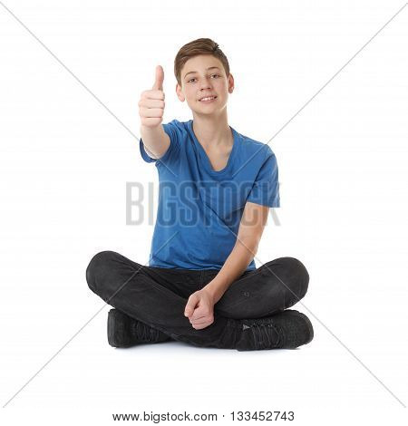 Cute teenager boy showing thumb up sign in blue T-shirt and lotus posture over white isolated background