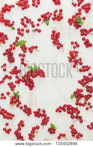 Red currants background. Fresh red currant on white wooden board. Overhead view, blank space