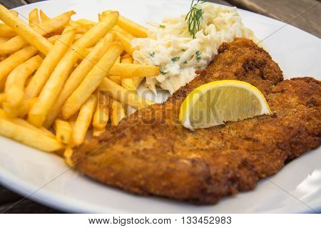 Fried fish and chips on the white plate on wooden table