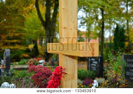 a provisional wooden cross on a fresh grave