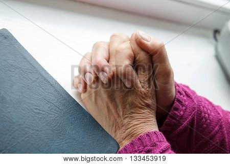 An old person praying to God with the Bible beside her