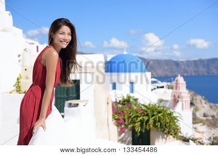 Santorini Thira Greece island tourism - Asian woman wearing red dress on summer travel looking at view with the famous attraction three domes chapel church in the background. Luxury destination.