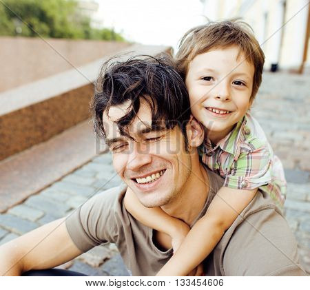 little son with father in city hagging and smiling, casual look outside playing, happy real family, lifestyle people concept close up