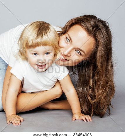 young pretty stylish mother with little cute blond daughter hugging, happy smiling real family, lifestyle people concept