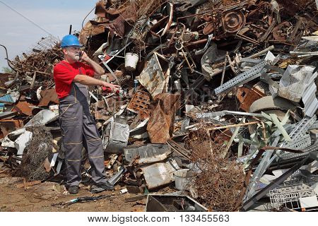 Recycling Industry, Worker Using Phone And Pointing