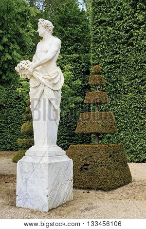 VERSAILLES, FRANCE - MAY 12, 2013: This is fragment of park area of Versailles with antique style's sculpture and topiary trees.
