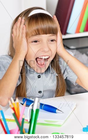 Education and school concept - shocked little student girl in school at the desk