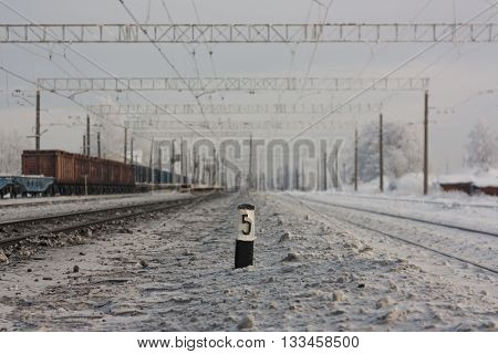 Electrified railway tracks -and railway station with traffic sign in winter period