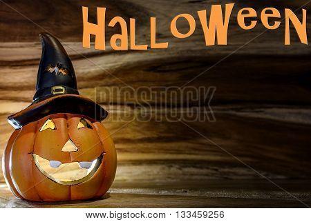halloween pumpkin on wood background candlelight in the dark with halloween written