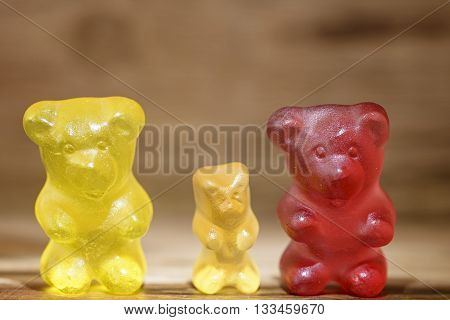 sweet gummy bear family on wooden background
