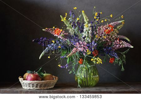 Still life bouquet with lupine and buttercups in a glass vase and basket of apples on wooden table.