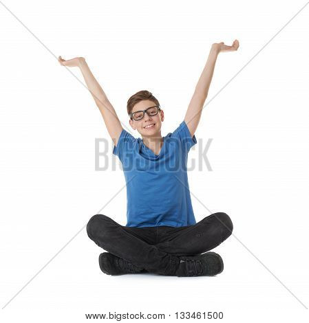 Cute teenager boy stretching hands up  in blue T-shirt, glasses and lotus posture over white isolated background