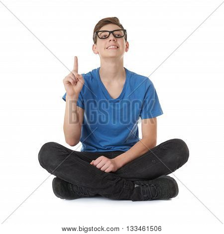 Cute teenager boy poinitng up in blue T-shirt, glasses and lotus posture over white isolated background