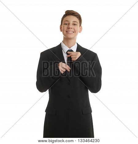 Cute teenager boy in back business suit correcting tie over white isolated background, half body, future career concept