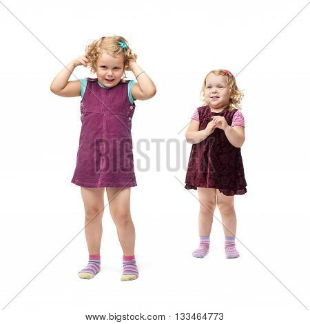 Couple of young little girls sisters with curly hair in purple dress standing over isolated white background