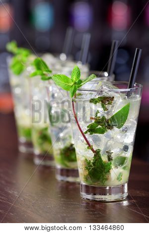 Row of four Mojito cocktails on a bar counter in a club. Vertical shot