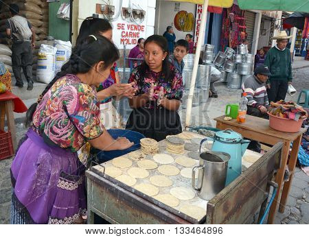 CHICHICASTENANGO GUSTEMALA APRIL 29 2016: Women cooking tortillas in the Chichicastenango Market. This native market is the most colorful in Central America