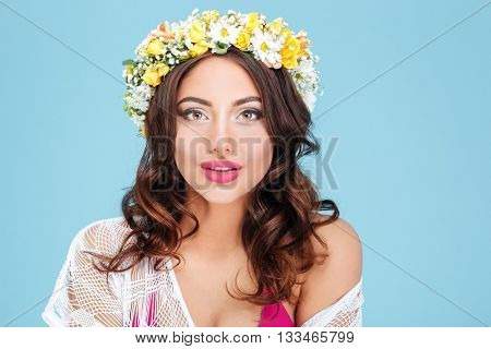 Close-up portrait of a sexy brunette wearing flower diadem isolated on the blue background