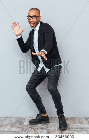 Young handsome man dancing isolated on the gray background