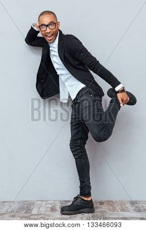 Young handsome man dancing and singing isolated on the gray background
