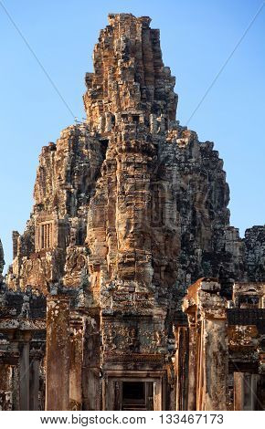 Dramatic view at sunset of one of the many large stone carved faces of Bayon Temple in Angkor Thom Angkor district Siem Reap Cambodia