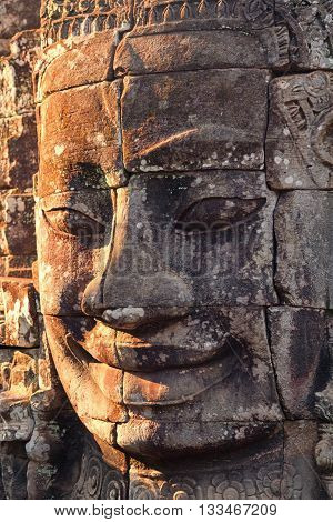 Close up view at sunset of one of the many large stone carved faces of Bayon Temple in Angkor Thom Angkor district Siem Reap Cambodia