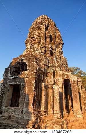 Stone carved face of Bayon Temple in Angkor Thom Angkor district Siem Reap Cambodia. Full length view