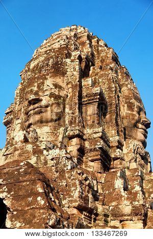 Stone carved face of Bayon Temple in Angkor Thom Angkor district Siem Reap Cambodia. Close up