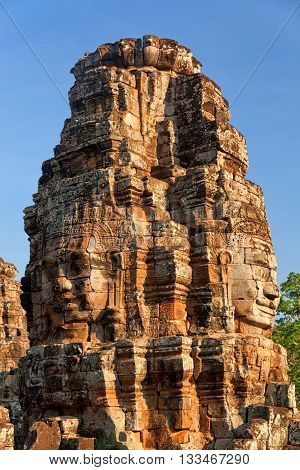Stone carved faces of Bayon Temple in Angkor Thom Angkor district Siem Reap Cambodia. Vertical shot sky on background. Shot at sunset