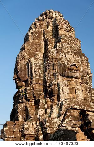 Stone carved faces of Bayon Temple in Angkor Thom Angkor district Siem Reap Cambodia. Vertical shot sky on background