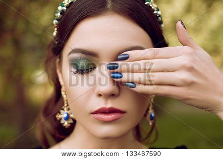 Portrait of beautiful woman, makeup and manicure in the same style, jewelry with precious stones. Makeup green, emerald and manicure is blue.