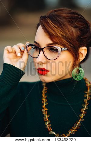 Portrait of young beautiful girl with glasses for vision. Beautiful bright makeup, green eyes, red plump lips. Green earrings, amber necklace, jewelry, accessories. Warm color toned