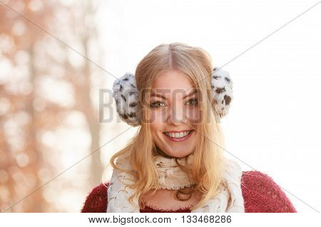 Portrait of pretty smiling fashionable woman in fall forest park. Happy gorgeous young girl in fur earmuffs. Autumn winter fashion.