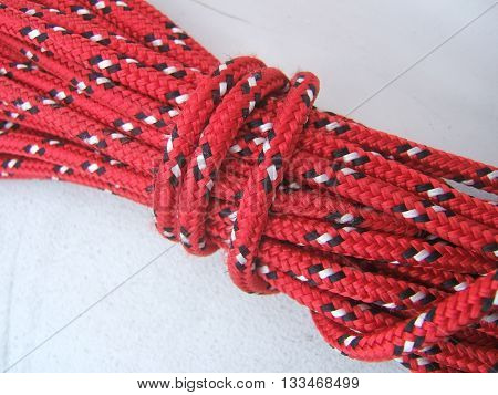 Coil of red marine rope for boats, photographed against the deck of a boat.